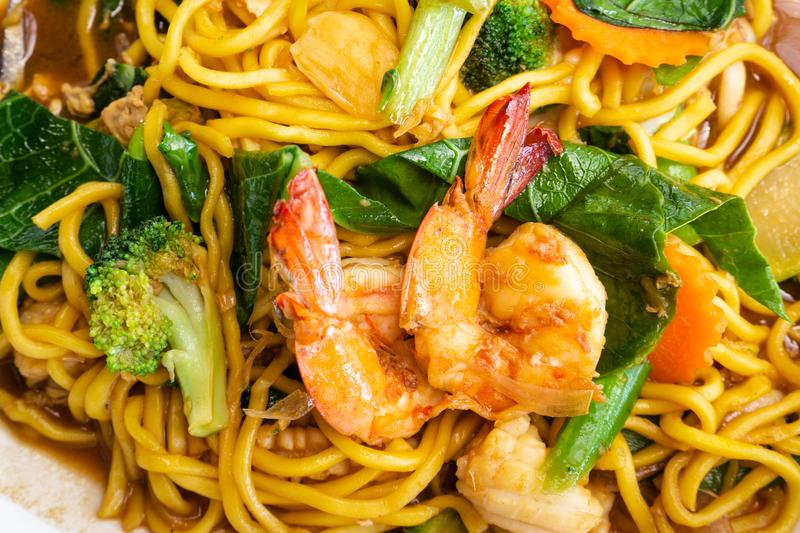 Close up delicious yellow fried noodles with soy sauce, prawns, vegetables and mushrooms. Thai stir-fried noodles Pad See-Ew. To. P view with copy space royalty free stock photography