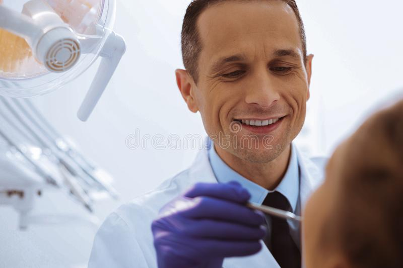 Close up of delighted assistant that checking teeth. Competent dentist. Portrait of handsome stomatologist that keeping smile on his face while treating his royalty free stock photos