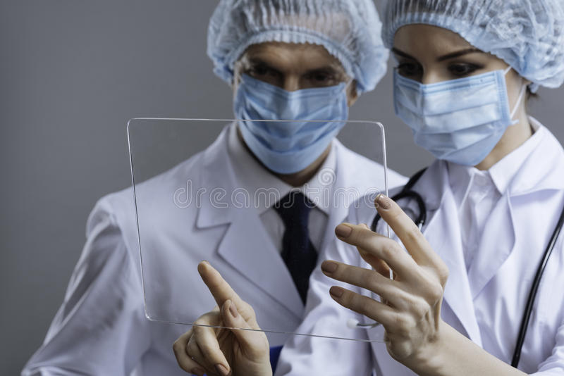 Close up of delighted colleagues using medical glass. Working together. Close up of delighted professional friendly colleagues using medical glass while wearing royalty free stock photo