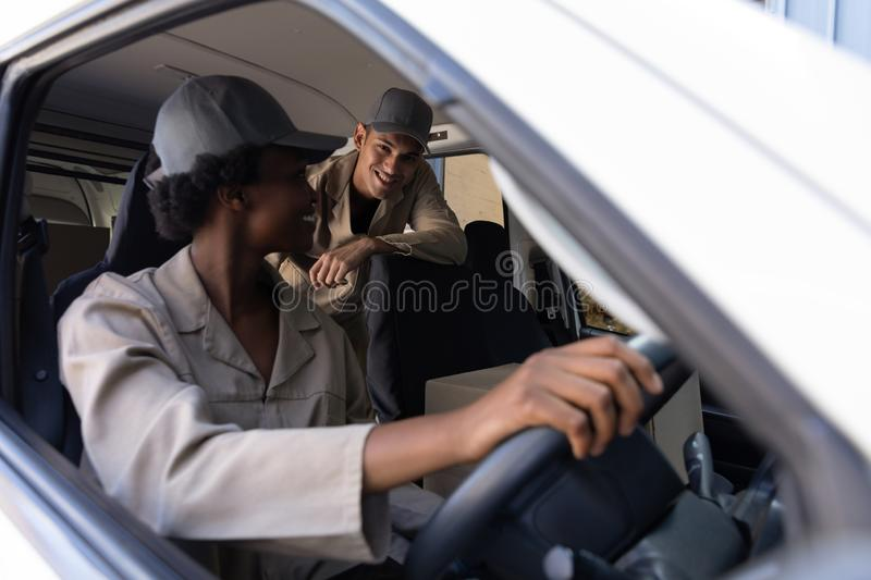 Delivery man and woman talking with each other in van outside the warehouse. Close-up of delivery man and woman talking with each other in van outside the royalty free stock photography