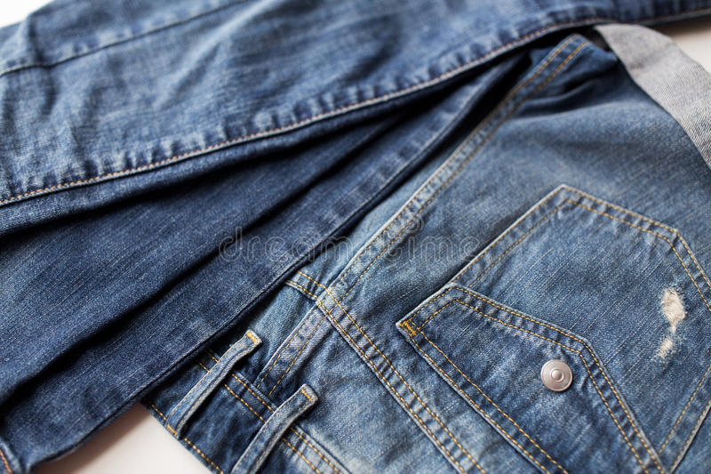 Close up of denim pants or jeans with pocket. Clothes, wear and fashion concept - close up of denim pants or jeans with pocket on white background royalty free stock photography