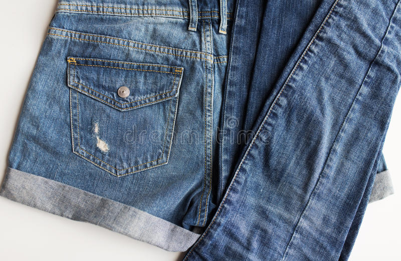 Close up of denim pants or jeans with pocket. Clothes, wear and fashion concept - close up of denim pants or jeans with pocket on white background stock image