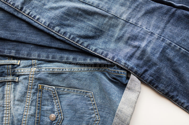 Close up of denim pants or jeans with pocket. Clothes, wear and fashion concept - close up of denim pants or jeans with pocket on white background royalty free stock image