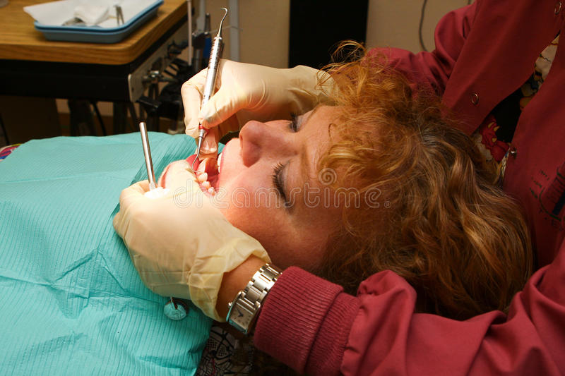 Close up of dental hygienist working on patient. A female woman with reddish curly hair lies back in a dental chair while a hygienist is using instrumants to royalty free stock photo