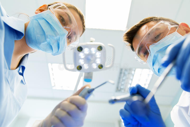 Close up of dentist and assistant at dental clinic. People, medicine, stomatology and health care concept - close up of dentist and assistant with dental mirror royalty free stock images