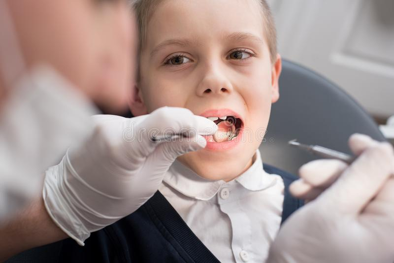 Pediatric dentist examining teeth of boy patient in dental clinic using dental tools - probe and mirror royalty free stock image