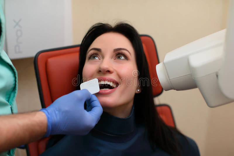 Close up of dentist putting intraoral shield to female patient mouth and assistant directing x-ray royalty free stock image