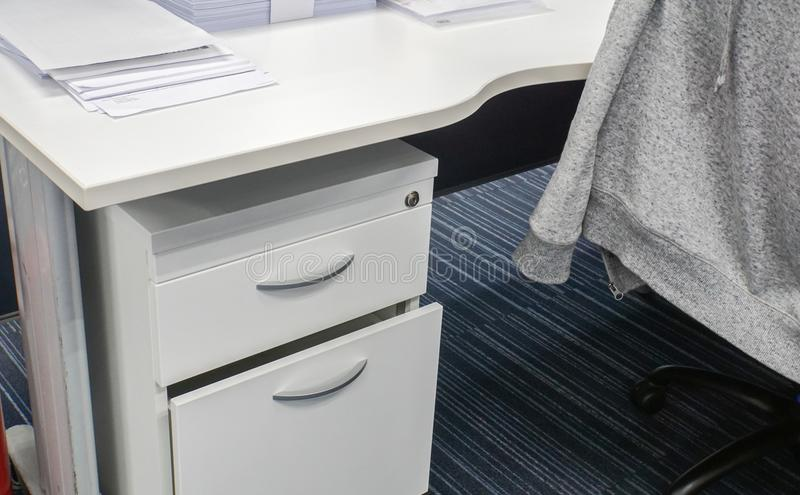 Desk drawer and office desk with jacket on chair. Close up desk drawer and office desk with jacket on chair royalty free stock photo