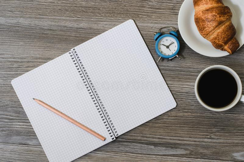 A close up of a desktop with blank notepad, alarm clock, cup of coffe and donut on it. Wooden background, top view stock photos