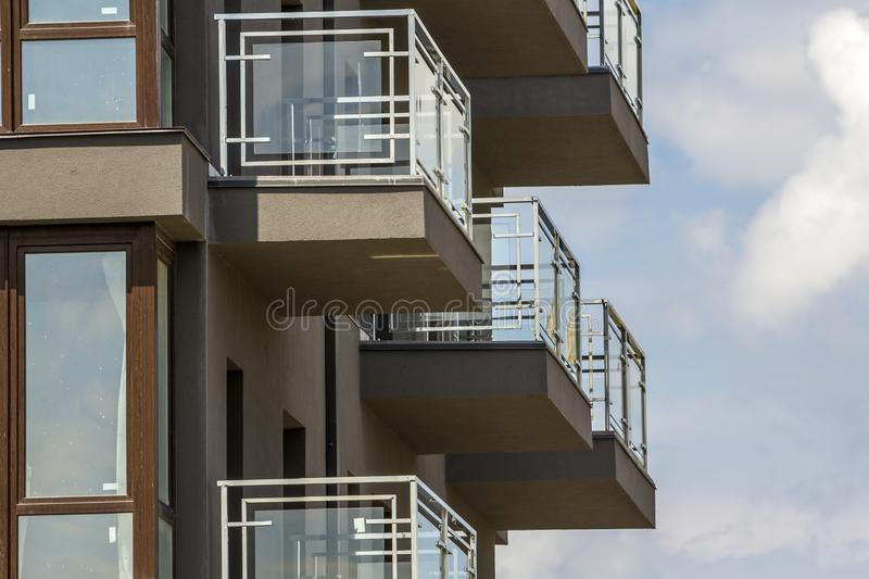 Close-up detail of apartment building wall with balconies and shiny windows on blue sky background. royalty free stock image
