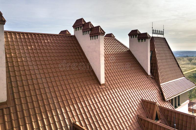 Close-up detail of building steep shingle roof and brick plastered chimneys on house top with metal tile roof. Roofing, repair and. Renovation work royalty free stock image