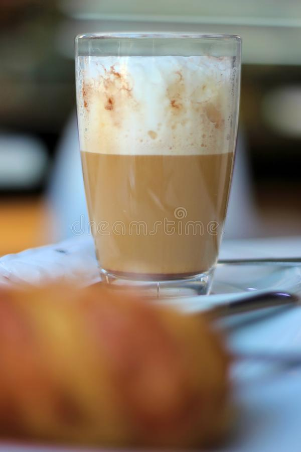 Close-up detail of a Cafe latte and a croissant on a coffee shop table royalty free stock images
