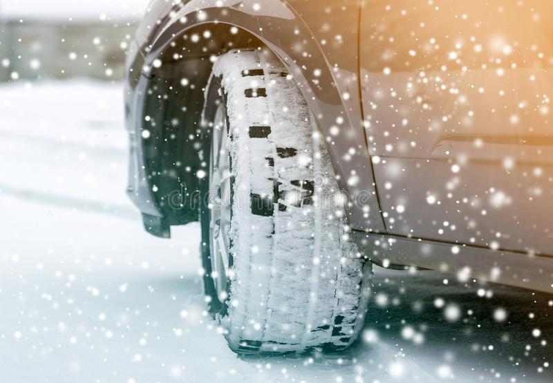 Close up detail car wheel with new black rubber tire protector on winter snow covered road. Transportation and safety concept.  stock images