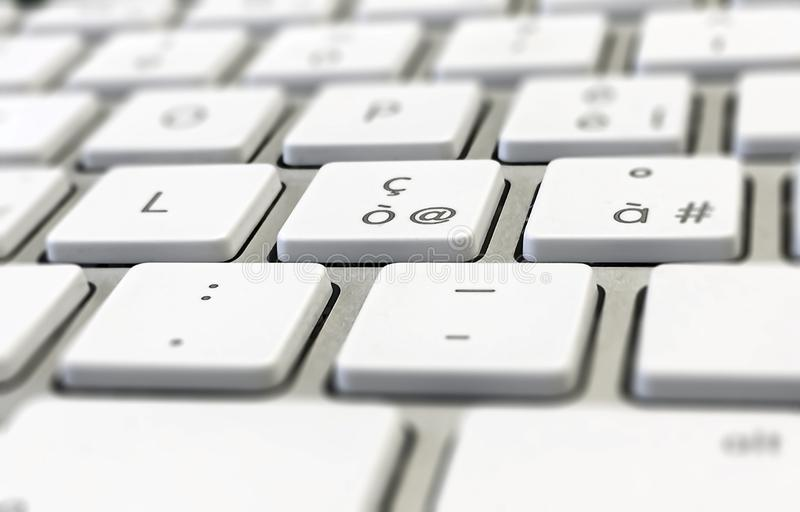 Close-up detail of a computer keyboard with white keys and a gray background stock images
