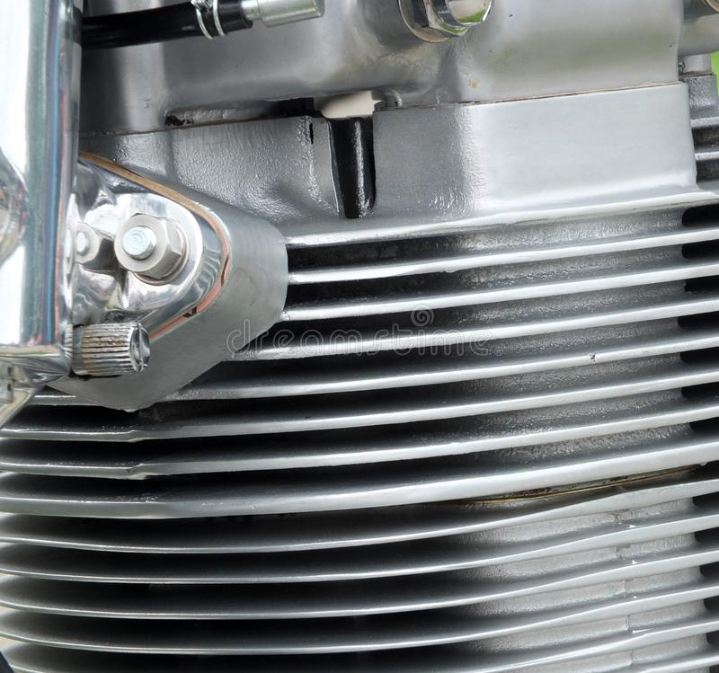 Close up detail of the cylinder head of an old motorcycle with silver fins and chrome bolts stock image