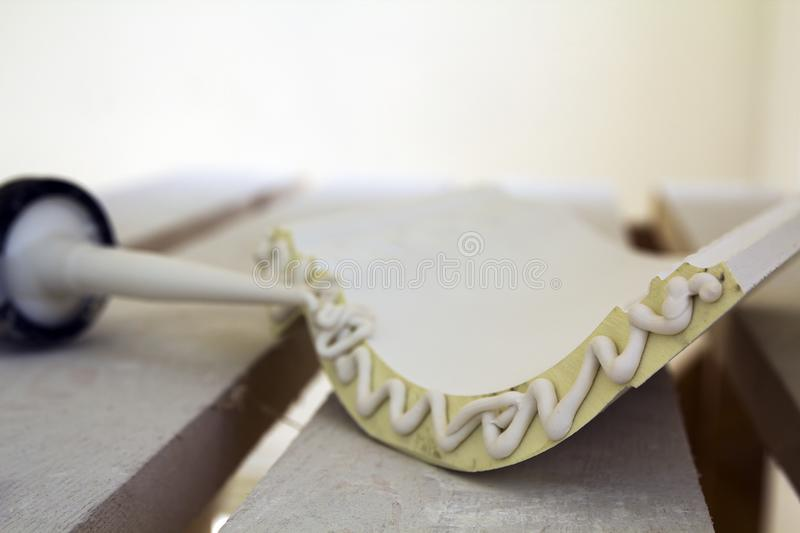 Close-up detail of decoration molding with glue adhesive before installation in interior renovation. Close-up detail of decoration molding with glue adhesive stock photography