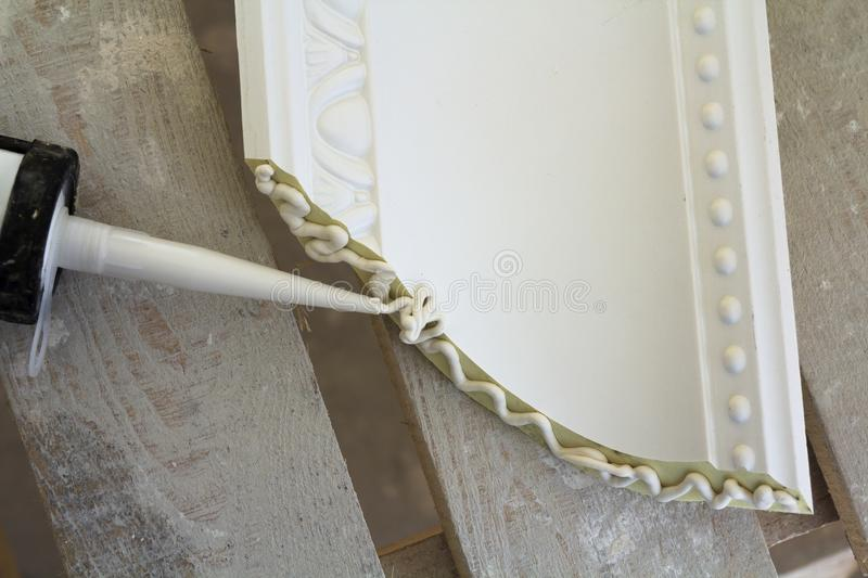 Close-up detail of decoration molding with glue adhesive before installation in interior renovation. Close-up detail of decoration molding with glue adhesive royalty free stock photo