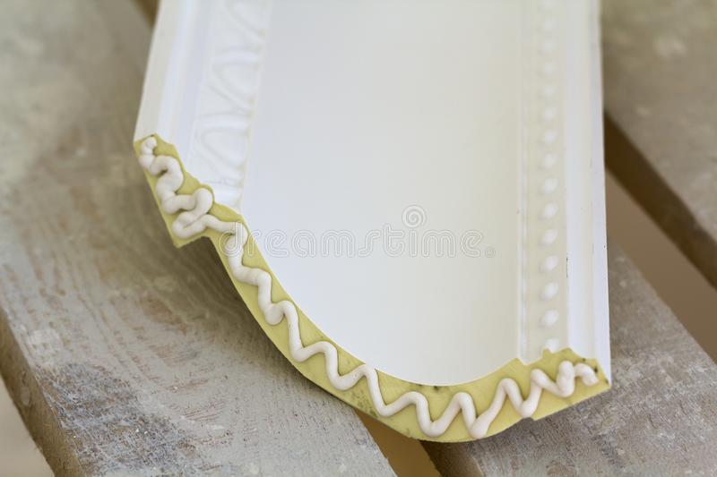 Close-up detail of decoration molding with glue adhesive before installation in interior renovation. Close-up detail of decoration molding with glue adhesive royalty free stock image