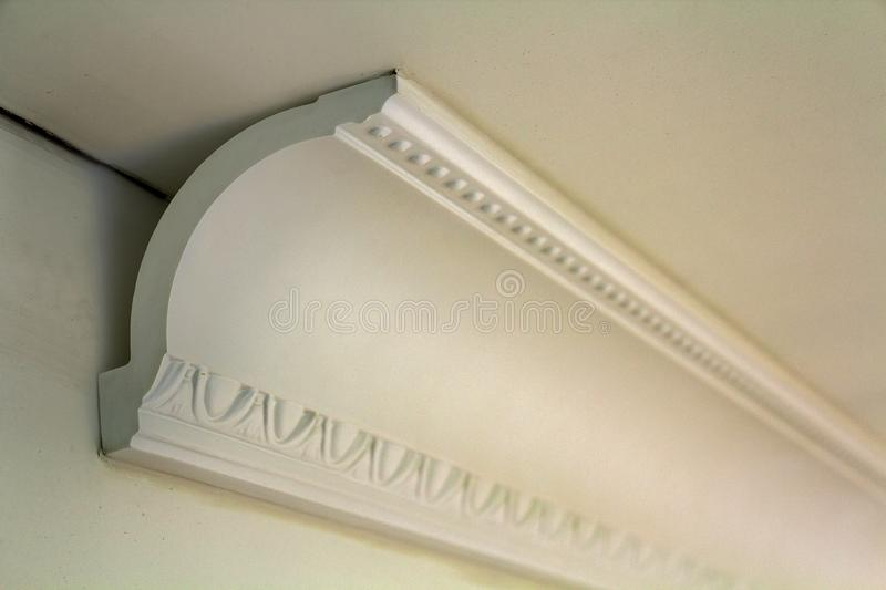 Close-up detail of decoration white molding connected with glue adhesive to wall and ceiling in interior room renovation and. Reconstruction royalty free stock image