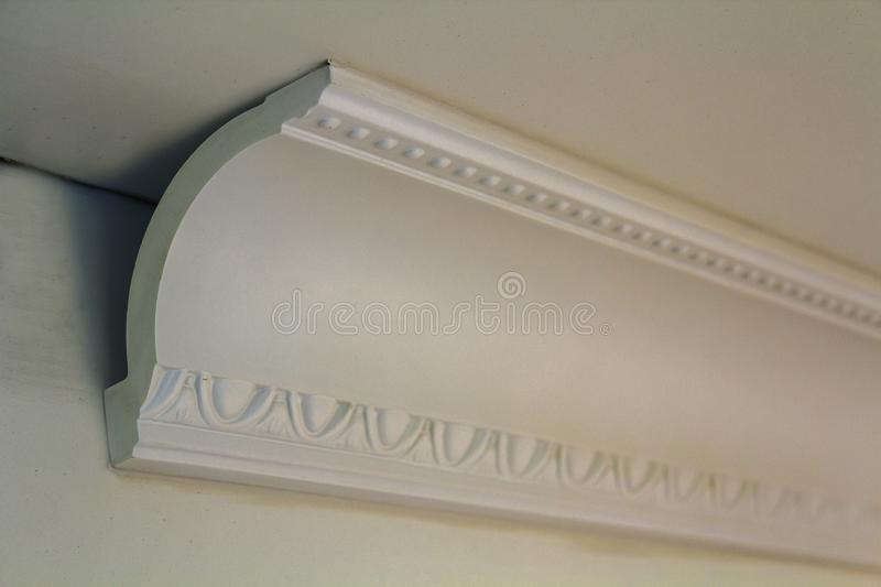 Close-up detail of decoration white molding connected with glue adhesive to wall and ceiling in interior room renovation and. Reconstruction stock images