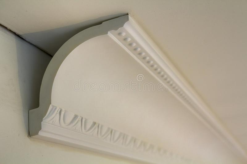 Close-up detail of decoration white molding connected with glue adhesive to wall and ceiling in interior room renovation and. Reconstruction royalty free stock photo