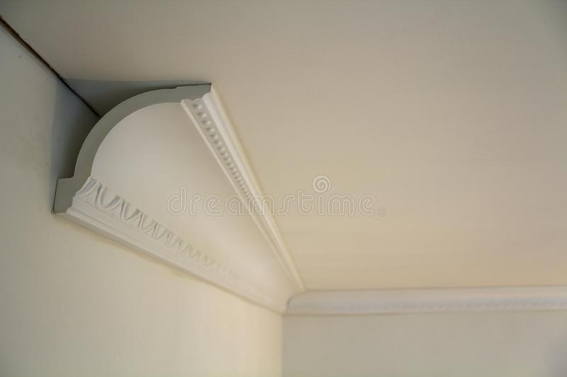 Close-up detail of decoration white molding connected with glue adhesive to wall and ceiling in interior room renovation and. Reconstruction stock photos