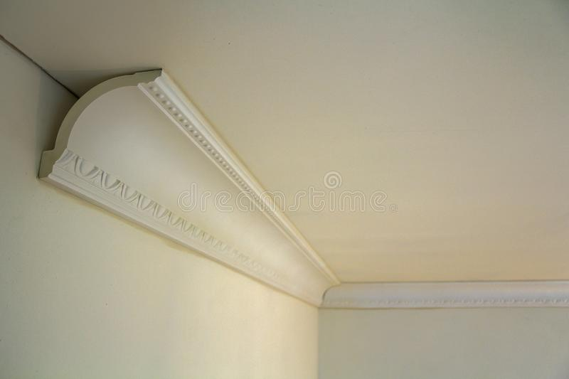 Close-up detail of decoration white molding connected with glue adhesive to wall and ceiling in interior room renovation and. Reconstruction royalty free stock images