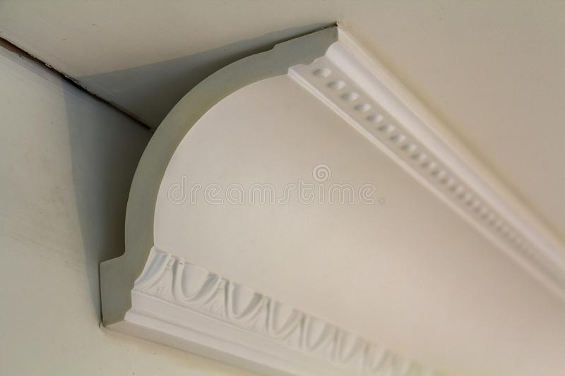Close-up detail of decoration white molding connected with glue adhesive to wall and ceiling in interior room renovation and. Reconstruction stock photography