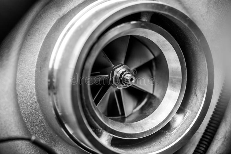 Close up detail of a diesel engine turbocharger with fan blades and center axle - selective focus on center axle stock image