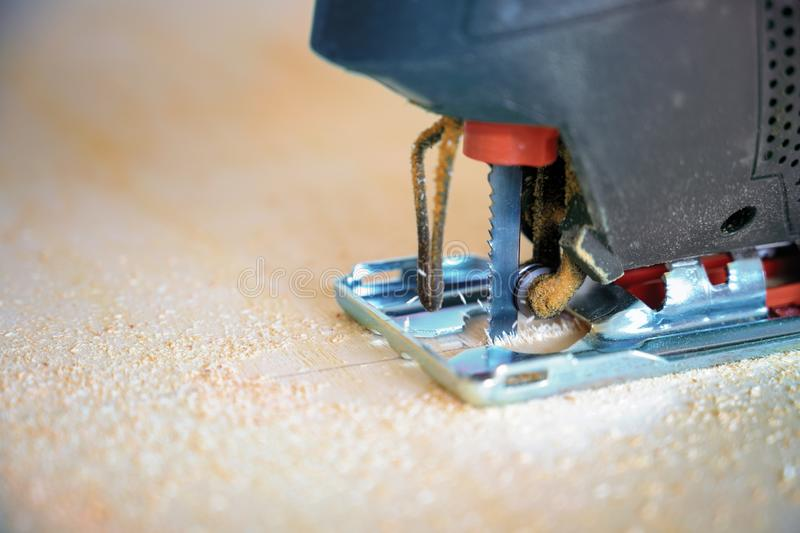 Close-up detail of an electric jigsaw sawing up a plywood board, tool for professional or hobby craft work, copy space stock photos