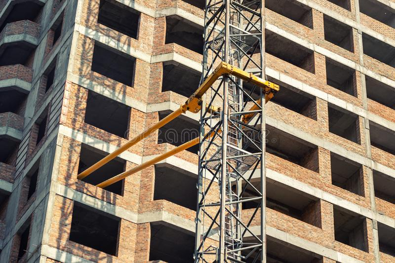 Close-up detail of highrise tower crane attached to building brick wall at hightower industrial construction site. Engineering and heavy machinery background royalty free stock images