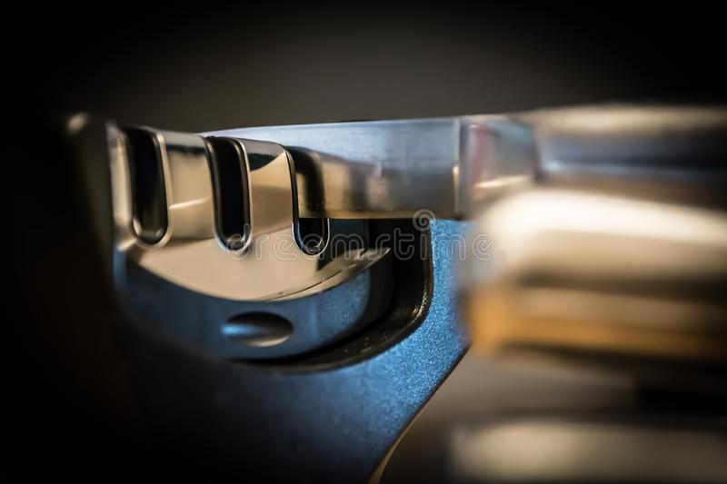 Close-up and detail of a knife in a knife sharpener kitchen tool. Metal and chrome. Blurred background stock photo