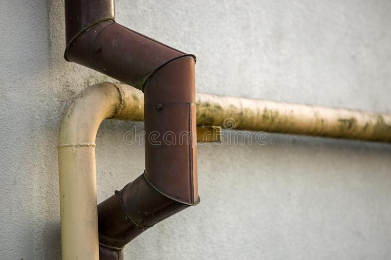 Close-up detail of old dirty painted yellow natural gas and brown gutter rain water pipes fastened to white house wall. Safety, da stock photos