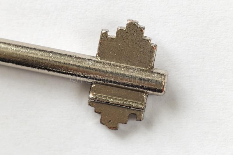 Close-up detail of old well-used steel key isolated on white copy space background. Safety and security concept royalty free stock photography