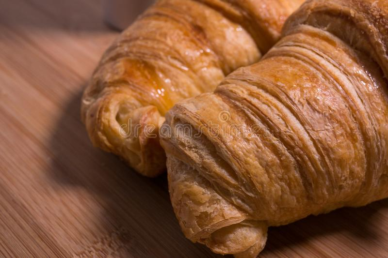 Close up / detail of a pair of French croissants on natural wood background royalty free stock photo
