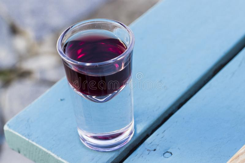 Close-up detail shot of small wine shot glass for purpose of taste in Turkey at afternoon. At sunset stock images