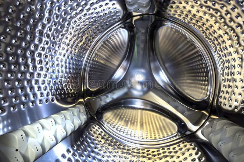 Close-up detail, stainless drum of modern washing machine interior. Abstract silver shiny surface design.  stock images