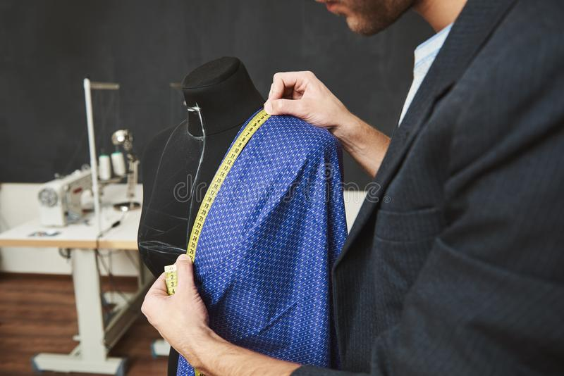 Close up detail of talented professional young caucasian male designer working on new dress for spring collection stock photography