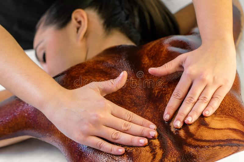 Hands massaging hot chocolate on female back royalty free stock photos