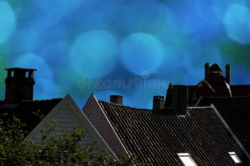 Close up detail of town house rooftops with chimneys against dark blue sky in the evening royalty free stock image