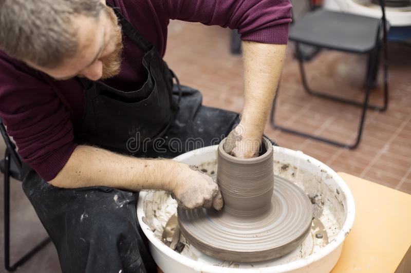 Artist makes clay pottery on a spin wheel. Close up detail view at an artist makes clay pottery on a spin wheel stock images