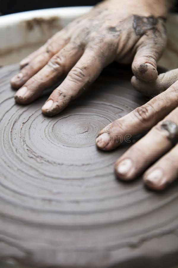 Artist makes clay pottery on a spin wheel. Close up detail view at an artist makes clay pottery on a spin wheel royalty free stock photography