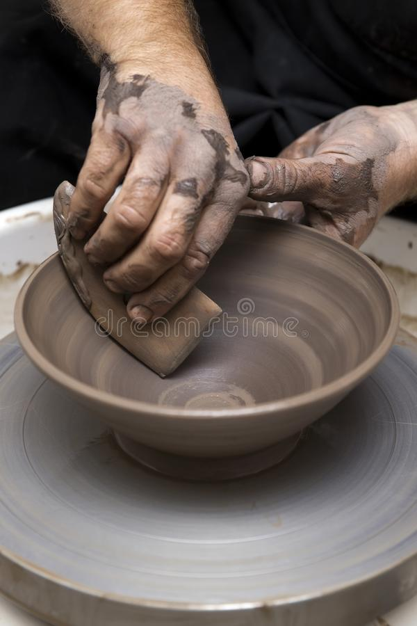 Artist makes clay pottery on a spin wheel. Close up detail view at an artist makes clay pottery on a spin wheel royalty free stock photo
