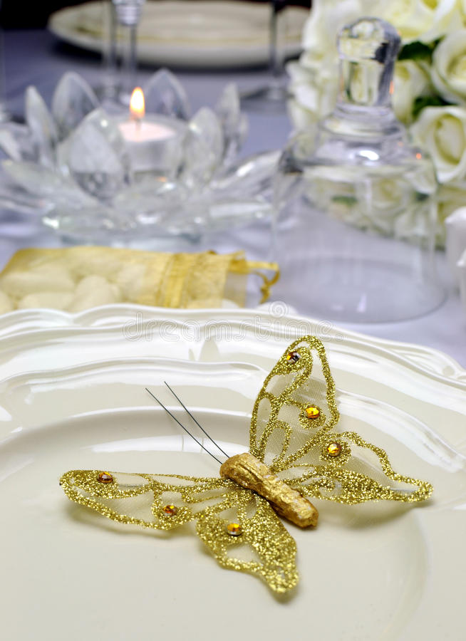 Close up of detail on wedding breakfast dining table setting with gold butterfly on china plates royalty free stock images