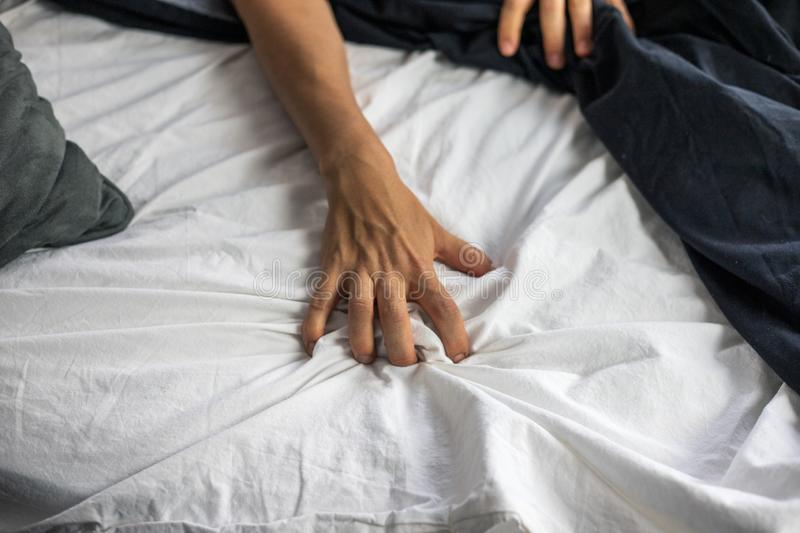 Close up detail of a women's hand grabbing on to the bed sheets, intimacy, erotic concept. Close up detail of a women's hand grabbing on to the bed royalty free stock photo
