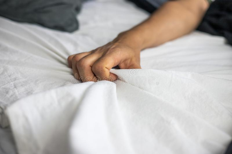 Close up detail of a womens hand grabbing on to the bed sheets, intimacy, erotic concept. Close up detail of a womens hand grabbing on to the bed sheets stock photo
