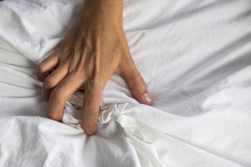 Close up detail of a womens hand grabbing on to the bed sheets, intimacy, erotic concept. Close up detail of a womens hand grabbing on to the bed sheets royalty free stock photography