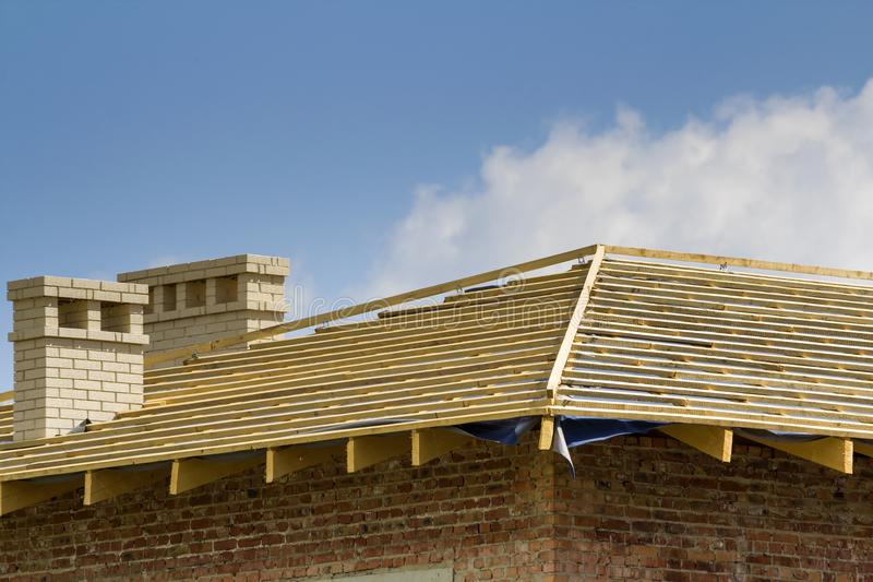 Close-up detail of wooden roof of new brick house with two white chimneys under construction. Timber frame of natural materials ag royalty free stock photography