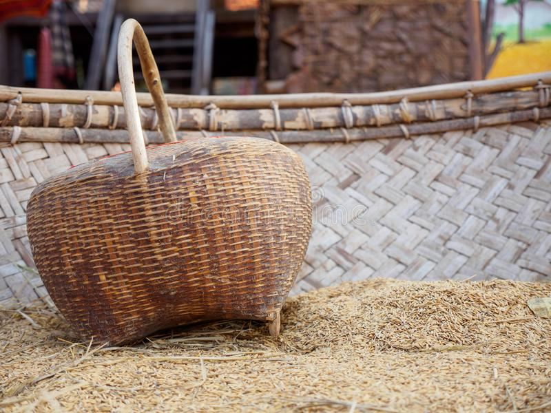 Wooden basket on rice hulls. Close-up detail of a woven bamboo basket on top of a pile of rice husks in a traditional wooden threshing and hulling machine royalty free stock photography