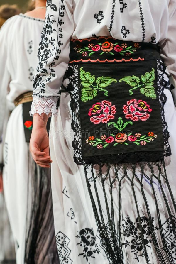 Close up on detail of young Romanian female dancer traditional folkloric costume. Folklore of Romania stock photography